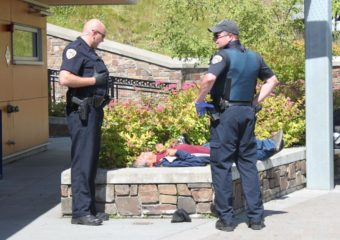 Two Juneau Police Department officers don gloves while they interact with a man lying down on Telephone Hill pocket park in July 2014. (Photo by Lisa Phu/KTOO)