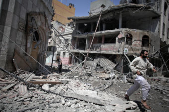 Palestinians walk through the rubble of houses in Gaza City minutes after they were hit in an Israeli strike on Wednesday. Khalil Hamra/AP