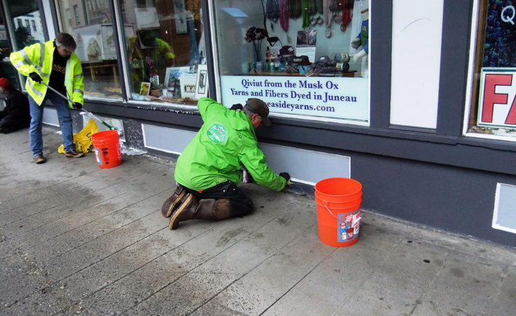 A volunteer scrubs away dirt and grime. (Photo by Rosemarie Alexander/KTOO)