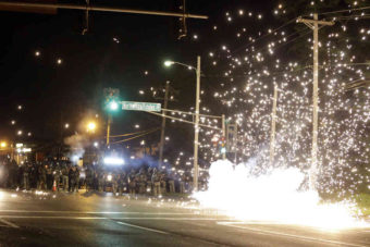 A device deployed by police goes off in the street as police and protesters clash Wednesday in Ferguson, Mo. Jeff Roberson/AP