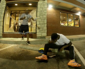 A man tries to recover from tear gas as people leave a McDonald's restaurant Sunday during a protest for Michael Brown in Ferguson, Mo. After police fired tear gas, people used bottles of water and milk to try to clear their eyes. Charlie Riedel/AP