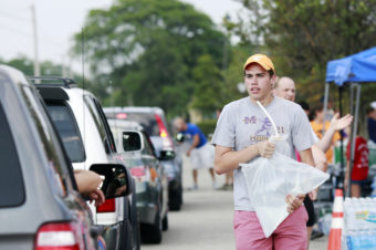 Grant Buehrer, a student at Ohio State University, volunteers to load a 5-pound bag of fresh drinking water into a vehicle on Sunday. Haraz N. Ghanbari/AP