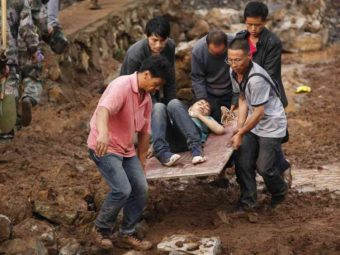 People carry an injured man through the debris in Ludian county in Zhaotong, a city in southwest China's Yunnan province on Monday.AFP/Getty Images