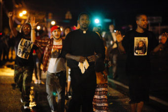 A clergyman leads demonstrators protesting the shooting death of Michael Brown down West Florissant Avenue in Ferguson, Mo., on Wednesday. A large contingent of clergy helped keep the mood calm after days of unrest. Eric Kayne for NPR