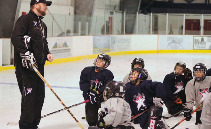 Rocky Mountain Hockey School coach Zac Desjardins gives instructions while Dylan Murdoch (center) and Joey Meir are fixed on the coach's words during the first week of the new season at Treadwell Ice Arena.