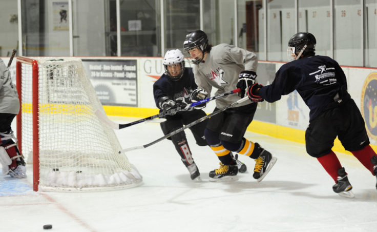 (from left) Culley Corrigan, Quin Gist and Shane Moller race for the puck during a three-on-three Rocky Mountain Hockey School drill at Treadwell Ice Arena.