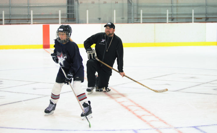 Rocky Mountain Hockey School coach Zac Desjardins watches over Taylor Bentley as she's about to receive a pass then relay it to another player during a Rocky Mountain High School drill at Treadwell Ice Arena.