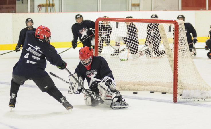 Gabe Miller runs into goalie Jaxson White during a Rocky Mountain Hockey School drill at Treadwell Ice Arena.