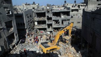 Palestinian emergency personnel dig through the rubble of a building destroyed by an Israeli military strike in Rafah in the southern Gaza Strip on Thursday. Hamas announced that three of its senior military commanders were killed in a predawn Israeli airstrike. Said Khatib/AFP/Getty Images