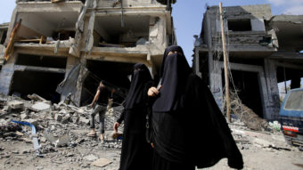 Palestinian women walk past the rubble of their homes in Gaza City's Shijaiyah neighborhood on Monday. An Egyptian-brokered cease-fire halting the Gaza war held into Monday morning, allowing Palestinians to leave homes and shelters as negotiators agreed to resume talks in Cairo. Hatem Moussa/AP