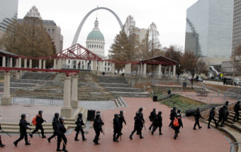 Officers wearing riot gear walk through a park in downtown St. Louis on Sunday. (Photo by Tom Gannam/AP)