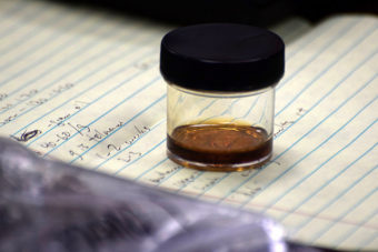 """A sample of marijuana hash oil, sits on the testifier's desk in an Alaska House Judiciary Committee hearing, March 6, 2015. The committee had asked law enforcement officials to give them a """"show and tell"""" about the drugs and associated paraphernalia. (Photo by Skip Gray/360 North)"""