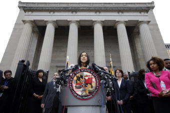 """Marilyn Mosby at a podium with the seal for the """"Office of the State's Attorney for Baltimore City"""""""