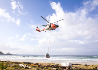 A Coast Guard helicopter lifts one of several bags of marine debris collected in 2014 on Biorka Island, near Sitka. (Photo courtesy Sitka Sound Science Center)