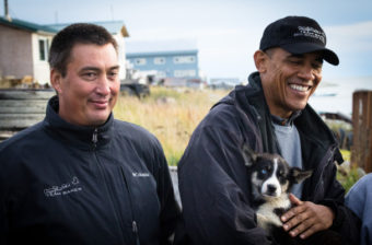 Iditarod musher John Baker meets President Barack Obama in Kotzebue, while Obama holds sled dog puppy Feather. (Photo by Matthew Smith/KNOM)