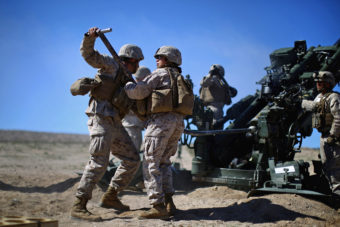 Defense Secretary Ash Carter is expected to announce that women can now serve in front-line combat posts. Here, Carolina Ortiz moves away from a 155-mm artillery piece after loading it during a live-fire exercise at the Marine base in Twentynine Palms, Calif., earlier this year, during a months-long study of how women might perform in ground combat jobs. David Gilkey/NPR