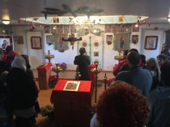 Subdeacon Ephim Moonin leading the Orthodox Christmas Eve celebration at Saint Sergius and Herman church in Nanwalek. (Photo by Daysha Eaton/KBBI)