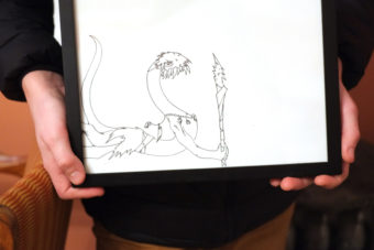 Ambrose Bucy holds one of his drawings from a past exhibition at the Alaska Robotics Student Show of the Comic Arts. (Photo by Annie Bartholomew/KTOO)