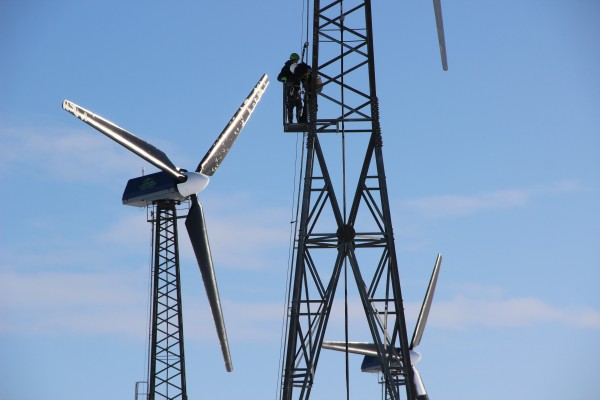 Patrick Boonstra of Intelligent Energy Systems, and Kwigillingok wind tech Benny Daniel check a turbine after a blizzard the night before. (Photo by Rachel Waldholz/APRN)