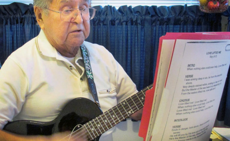 Ketchikan's Fred John sings and plays a gospel song in his kitchen. He's volunteered at Ketchikan's prison and other locations. (Photo by Leila Kheiry/KRBD)