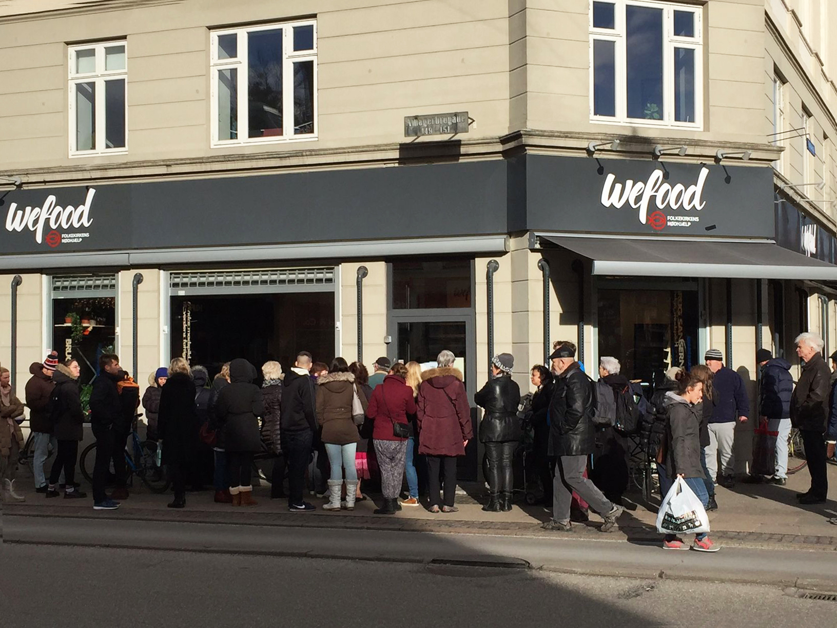 A crowd waits on the sidewalk for the WeFood grocery store