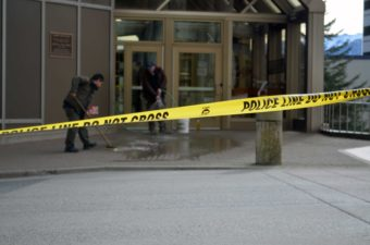 Two men clean the sidewalk outside the Dimond Courthouse Monday. Police say 34-year-old Miranda Ellen Davison intentionally shot herself in the chest. (Photo by Jennifer Canfield/KTOO)