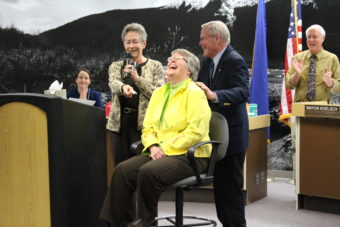 Former Juneau mayor Sally Smith presents Kim Kiefer with $50. (Photo by Elizabeth Jenkins/KTOO)