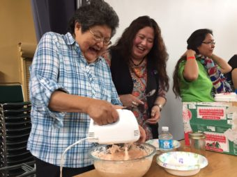 Doris McLean of Whitehorse whips up a jar of soapberries, which took first prize at Sealaska Heritage's contest. Next to her is Leonilei Abbott, daughter of Helen Watkins, who was widely known for teaching about native foods. (Photo by Emily Kwong/KCAW)