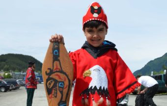 This is Roary Earl Bennett's first joining the One People Canoe Society. He hand-carved his paddle and painted on it a killer whale, representing his grandfather's house. Photo by Emily Kwong/KCAW)