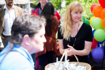 Pride Committee member Jenny Jahn collects candles after the ceremony ended. (Photo by Annie Bartholomew/KTOO)