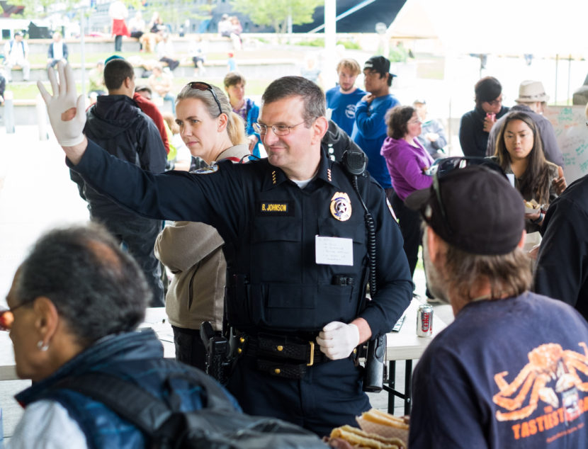 """Juneau Chief of Police Bryce Johnson waves at a community barbecue held in Marine Park to """"be counted as a person against violence, against discrimination, and against hate,"""" according to the Juneau Police Department Facebook page, July 20, 2016. (Photo by Annie Bartholomew/KTOO)"""
