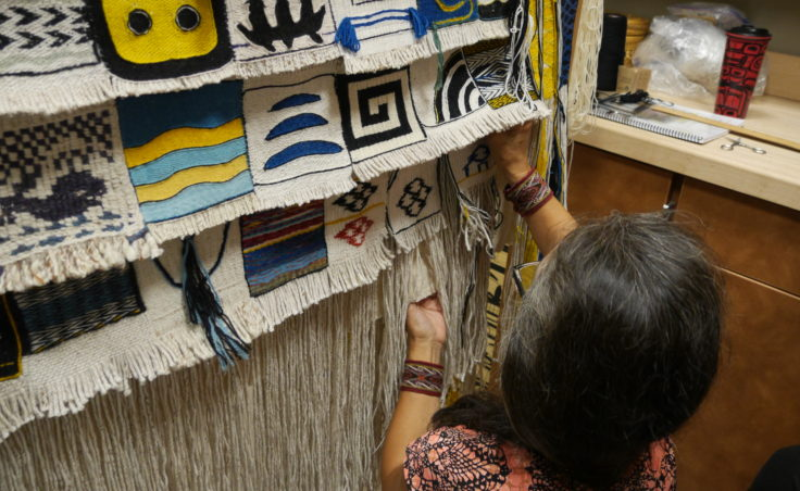 Clarissa Rizal unpins a block to show the details in the weave. (Photo by Tripp J Crouse/KTOO)