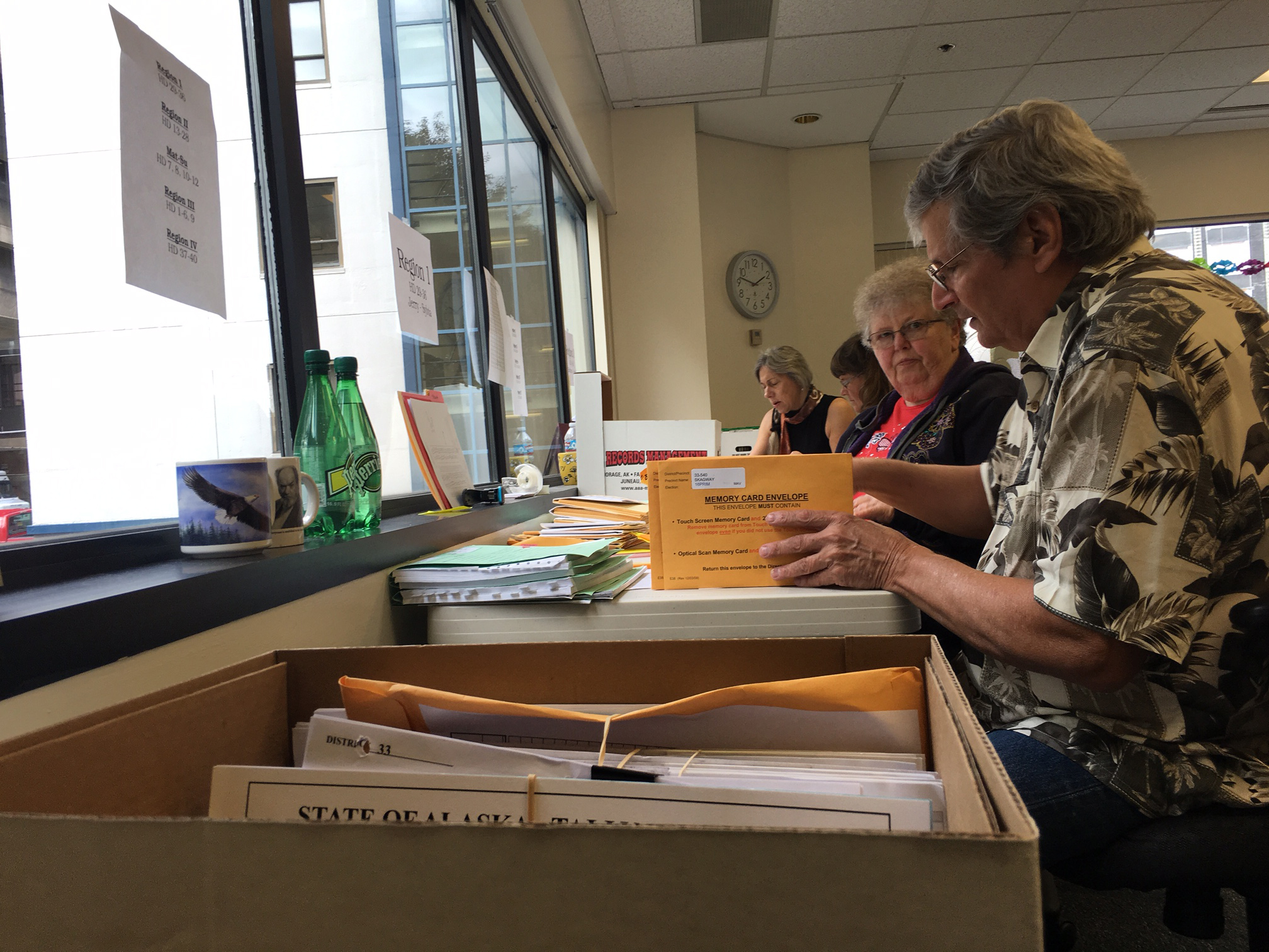 Election review board members sort through election materials at the Division of Elections office in Juneau, Aug. 30, 2016. (By Andrew Kitchenman/KTOO)