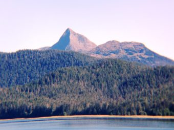 A mountain peak rises above the Tongass National Forest northeast of Sitka Aug. 3, 2016. (Photo by Ed Schoenfeld/CoastAlaska News)