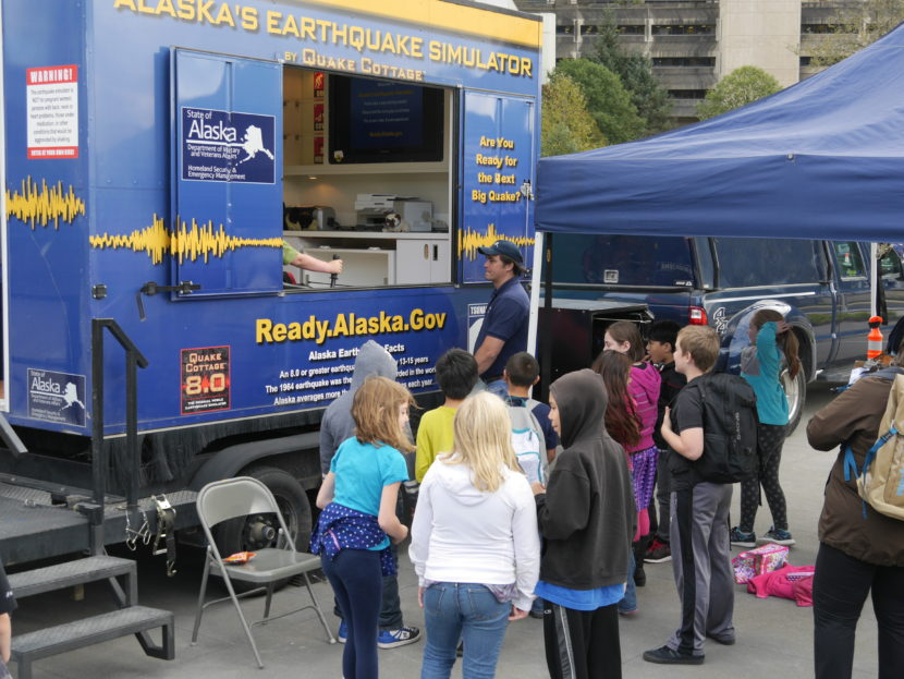 A young crowd gathers around the earthquake simulator on Wednesday, August 31, 2016. The emergency preparedness and awareness event was hosted by Alaska Division of Homeland Security and Emergency Management and Juneau Local Emergency Planning Committee. (Photo by Tripp J Crouse/KTOO)