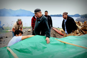Master carver Steve Brown oversaw the steaming, while Jerrod Galanin takes a look under the tarp. (Photo by Emily Russell/KCAW)