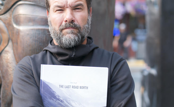 A man in front of a totem holds a book. Juneau photographer Ben Huff holds his book 'The Last Road North' following the demonstration against budget cuts to the Alaska State Council on the Arts. (Photo by Annie Bartholomew/KTOO)