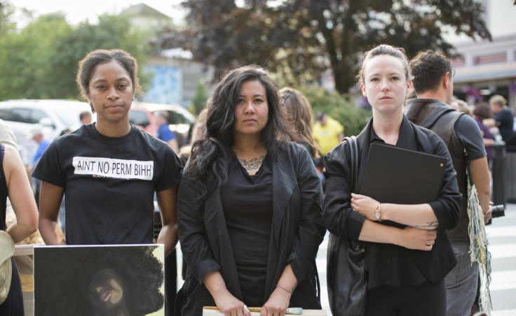 Three women dressed in black stand on a street corner. Juneau artists Jennifer Gross, Christianne Carrillo, and Cate Ross stand outside the Sealaska Heritage Institute following a demonstration protesting the budget cuts to the Alaska State Council on the Arts on Tuesday, July 9, 2019. (Photo by Annie Bartholomew/KTOO)