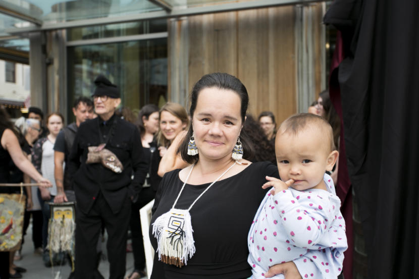 "A woman holds her baby on a street corner in Juneau. Master Chilkat Weaver Lily Hope holds her daughter at the peaceful demonstration opposing the budget cuts to the Alaska State Council on the Arts outside Sealaska Heritage Institute on Tuesday, July 9, 2019. Hope helped organize the event which covered the totems with black fabric to create a public art ""black out."" Photo by Annie Bartholomew/KTOO."