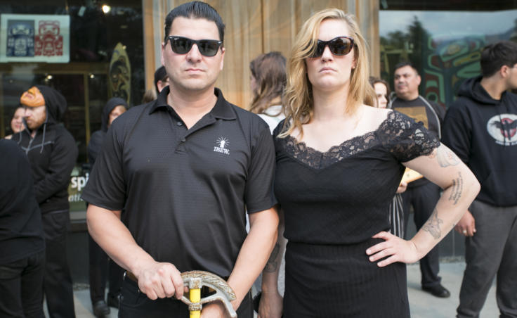 "A man and woman wearing black stand on the street Assistant Business Manager for the International Brotherhood of Electrical Workers Local 1547 union and Juneau performance artist Rachel Byrd stand outside Sealaska Heritage Institute at the demonstration and public art ""black out"" on Tuesday, July 9, 2019. (Photo by Annie Bartholomew/KTOO)"