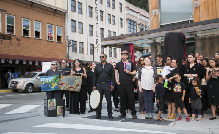 A photo of people holding books, painting, drums and art on a street corner. They are dressed in black.