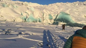 Yana White's mother stands on thin ice near a freshly calved section of the face of Mendenhall Glacier on Dec. 11, 2016. Houston Laws is in the foreground, moments before falling into the lake himself. (Photo courtesy Houston Laws)