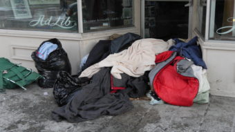 A pile of blankets in the doorway of a business on Franklin Street in downtown Juneau. (Photo by Quinton Chandler/KTOO)