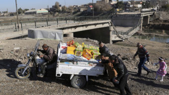 Men push a cart at a makeshift river crossing next to a bridge destroyed by Islamic State militants in Mosul, Iraq, on Thursday. The Iraqi forces have reclaimed much of eastern Mosul, but the Islamic State still controls much of the western side of the city.