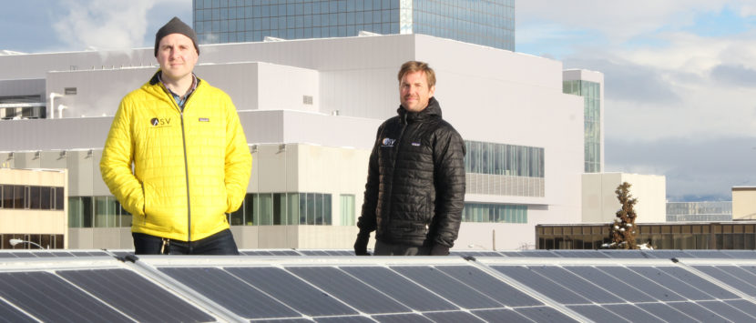 Stephen Trimble and Chase Christie of Arctic Solar Ventures show off the company's largest installation to date: an 86-panel commercial installation in downtown Anchorage. (Photo by Rachel Waldholz/Alaska's Energy Desk)