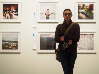 """Photographer Brian Adams stands before a few of the 50 images featured in the Anchorage Museum's exhibition for his """"I Am Inuit"""" project. (Photo by Zachariah Hughes/Alaska Public Media)"""