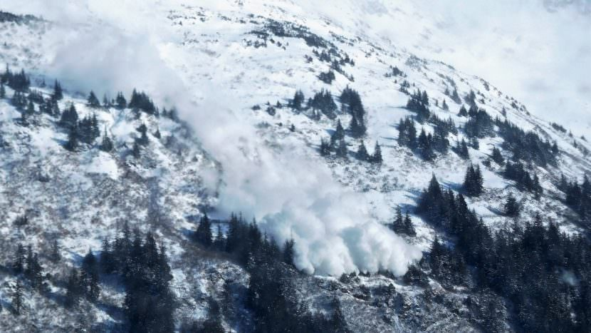 An avalanche triggered by a state crew slides down the slopes of Mount Roberts above Thane Road on March 3, 2017. The cloud of snow crossed the channel to Douglas. (Photo by Ed Schoenfeld, CoastAlaska News)