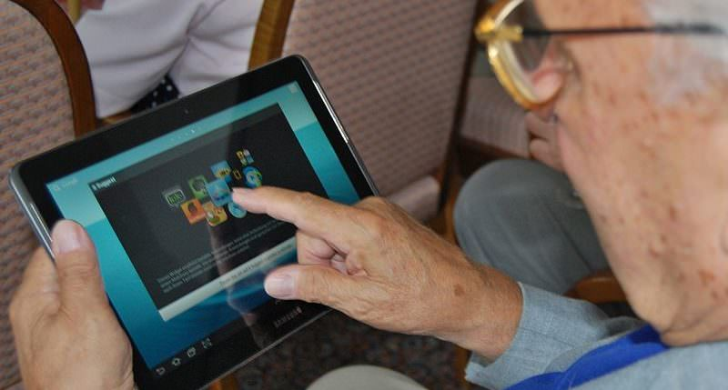 An elderly person uses a tablet. (Photo by Sigismund von Dobschütz/Wikimedia Commons)