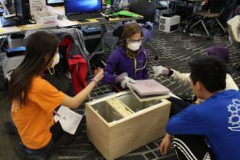 ANSEP Academy students have to wear masks and gloves when operating the heat lamps and using the various materials. (Photo by Wesley Early, Alaska Public Media – Anchorage)
