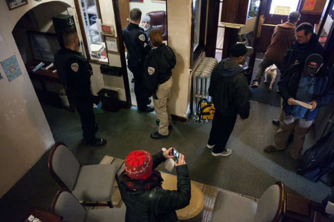 Police, aid workers, journalists and tenants of the Bergmann Hotel gather in the lobby as the building is cleared and boarded up on Friday, March 10, 2017 in Juneau, Alaska.